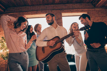 Company of nice-looking lovely charming elegant classy cheerful cheery ecstatic positive careless guys ladies having fun birthday event disco guitar player in industrial loft interior room indoors
