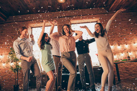 Portrait of nice great cool company pretty charming attractive cheerful cheery glad positive guys ladies having fun disco flying decorative elements rejoice rest relax day in industrial loft interior