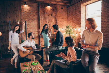 Close up photo gathering best friends buddies hang out vocal soloist play guitar dancing flirty girlish cute she her ladies he him his guys wear dresses shirts formal wear sit sofa loft room indoors Stock Photo