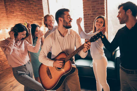 Close up photo classy gathering hang out overjoyed guitar play performance dancing old legends popular songs rest relax she her ladies he him his guys wear dress shirts formal wear loft room indoors
