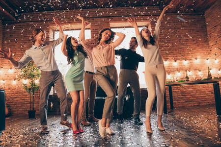 Full length body size view of nice company pretty charming attractive cheerful glad positive guys ladies having fun disco flying decorative elements rejoicing in industrial loft interior house Stock Photo