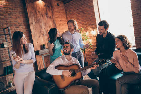 Close up photo drunk seldom long waited gathering best friends buddies hang out vocal soloist play guitar she her ladies he him his guys wear dresses shirts formal wear sit sofa loft room indoors Stock Photo