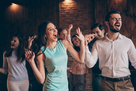 Close up photo classy gathering hang out dance singing look watch see karaoke words screen yell scream shout she her ladies he him his guys wear dress shirts formal wear sit sofa loft room indoors Imagens - 119456004