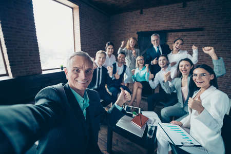 Self-portrait of nice stylish cheerful excited glad executive company staff showing thumbsup yes goal corporate culture agree advice at modern industrial loft interior work place space Stockfoto