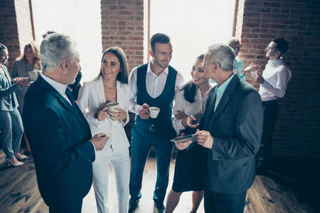 Close up photo morning diversity age mixed race business people stand she her he him his best brigade conversation tell speak over company news listening reading beverage formal wear jackets shirts