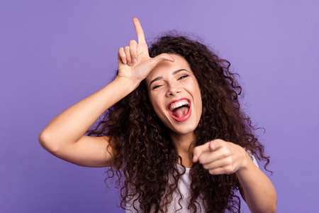 Close up photo beautiful her she lady index finger point you hand show loser symbol on forehead laughing out loud impolite wear casual white t-shirt clothes outfit isolated violet purple background