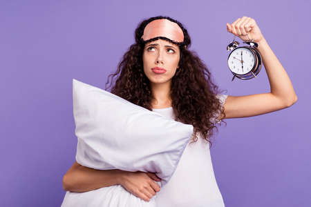 Portrait of her she nice cute charming attractive depressed brunette wavy-haired lady holding in hands pillow clock isolated on bright vivid shine violet purple background Standard-Bild