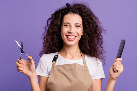 Close up photo pretty beautiful her she lady hold hands arms haircut equipment sincerely toothy smiling guests clients customers wear casual white t-shirt apron isolated violet purple background 스톡 콘텐츠
