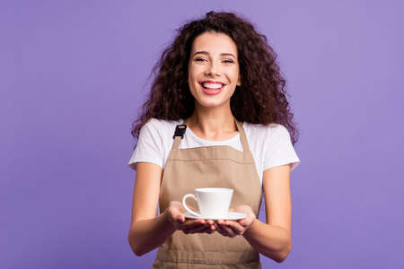 Close up photo pretty beautiful her she lady cafeteria hands arms glass cup hot beverage look invite propose guests rest relax laugh wear casual white t-shirt apron isolated violet purple background Stock Photo