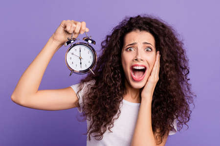 Close-up portrait of her she nice cute charming attractive crazy mad devastated brunette wavy-haired lady showing clock hurry oops isolated on bright vivid shine violet purple background