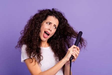 Portrait en gros plan d'une jolie jolie jolie dame aux cheveux ondulés confuse utilisant un nouveau produit électrique repasseur chaud à haute température isolé sur fond pastel violet brillant et brillant