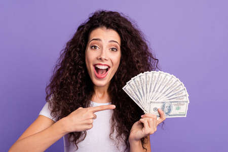 Close-up portrait of nice cute attractive lovely cheerful cheery wavy-haired lady holding in hand showing big large sum of money budget isolated on bright vivid shine violet pastel background 스톡 콘텐츠