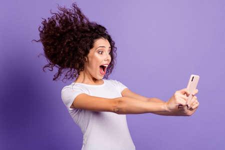 Portrait d'elle, elle est belle, jolie, gaie, gaie, drôle, folle, femme aux cheveux ondulés, tenant dans la main des cellules cellulaires prenant un selfie isolé sur un fond pastel violet brillant et brillant