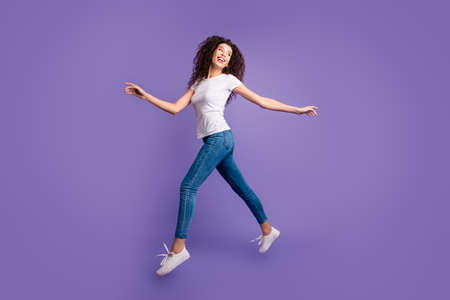 Full length side profile body size photo funky beautiful she her lady jump high spread hands arms shopping store mall wear casual jeans denim white t-shirt sneakers isolated purple violet background