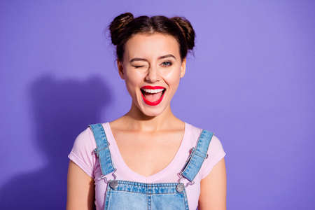 Close up photo beautiful amazing she her lady two buns open mouth wink boys guys cheerful pretty red lips pomade wear casual t-shirt jeans denim overalls clothes isolated purple violet background