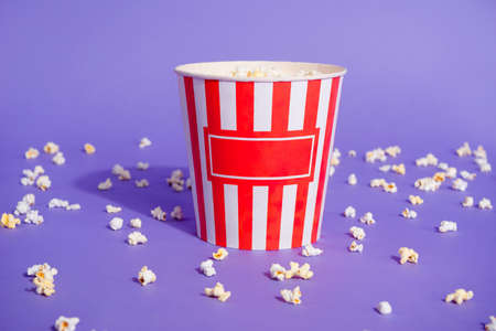 Close up photo of tasty salted sugary different mixed tastes popcorn in striped paper cup little small pieces thrown everywhere isolated on purple violet bright background