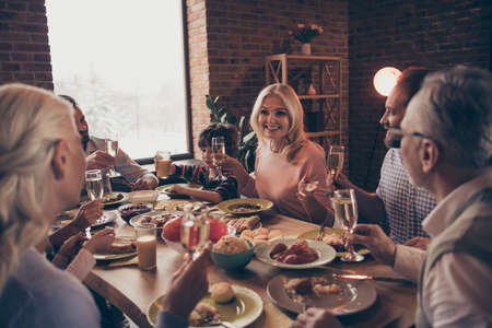 Close up photo big family birthday toast raise wineglasses golden beverage members brother sister granny mom dad grandpa little son daughter sit round festive holiday dishes table loft house indoors
