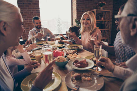 Close up photo big family birthday toast raise wineglasses golden beverage members brother sister granny mom dad grandpa little son daughter sit round festive holiday dishes table loft house indoors Stock Photo