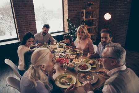 Close up photo big large family thanksgiving conversation members company brother sister granny mom dad grandpa son daughter sitting round festive holiday full tasty dishes table loft house indoors Zdjęcie Seryjne - 120814235