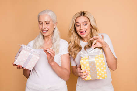 Portrait of cute pretty ladies got wrap giftboxes ribbon dot 8-march anniversary have party feel glad satisfied isolated wear trendy stylish clothes on beige background