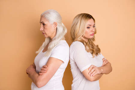 Profile side view portrait of nice-looking attractive lovely gloomy grumpy moody bored tired ladies wearing white outfit folded arms isolated over beige pastel background