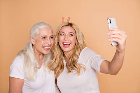 Close-up portrait of nice lovely attractive charming cute cheerful cheery playful comic ladies wearing white t-shirt taking making selfie showing v-sign bunny ears isolated on beige pastel background