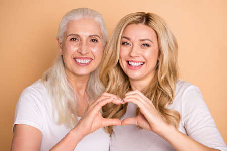 Nahaufnahmeporträt von gut aussehenden, hübschen, attraktiven, süßen, charmanten, fröhlichen, fröhlichen Damen, die ein weißes T-Shirt tragen, das ein romantisches Herzzeichen einzeln auf beige pastellfarbenem Hintergrund zeigt Standard-Bild
