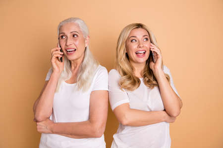 Portrait of nice-looking lovely adorable attractive charming cute cheerful cheery glad ladies wearing white t-shirt talking with boyfriend roaming cellular isolated over beige pastel background Standard-Bild