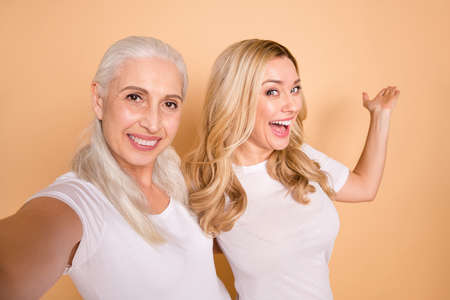 Close up portrait of cute excited adults bloggers advertise decide advise choose suggest give feedback decision indicate hug stylish lifestyle wear modern t-shirts beige background isolated Foto de archivo