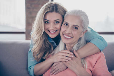 Close up photo two amazing she her ladies mom child granny grandmother hugging piggy back missed wait meeting long time wear casual domestic clothes sit comfy cosy couch divan flat house indoors
