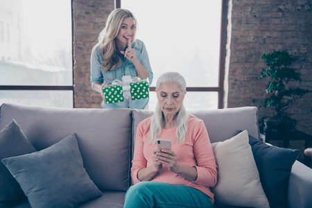 Close up photo two amazing she her ladies mom child grandmother use app not wait grandchildren holiday not see back giftbox daughter casual domestic clothes sit comfy couch divan flat house indoors