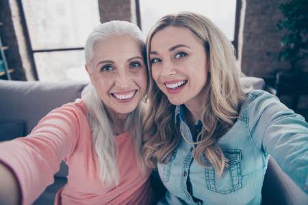 Cerrar foto dos hermosas ella sus damas funky abuela nieta parientes mamá mami hacer tomar selfies teléfono manos brazos buen humor sentarse sofá diván sofá casa adentro