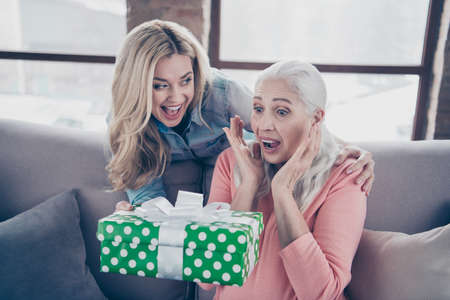 Close up photo two people she her ladies mom child grandmother grandchildren holiday giftbox not expect visit come cry gladness casual domestic clothes sit comfy couch divan flat house indoors