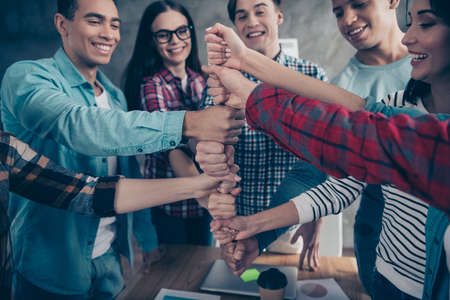 Optimistic positive joyful unity of college students girl guys race having doing coaching exercises happy smile wear casual shirts situated in modern office placing fists together