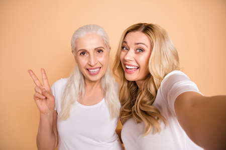 Close up photo of funny charming adults bloggers have fun free time feel satisfied excited enjoy get unforgettable moments make v-signs hug curly trendy clothes isolated beige background