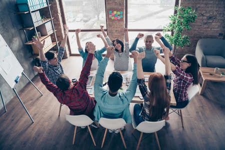 Gathering millennial girls managers professionals having wining strategy excited screaming yeah gesturing raising fists dressed in casual shirts in pretty office