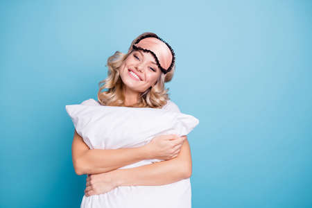 Close up photo beautiful funky her she lady white teeth hands arms palms hold cuddle big large pillow glad day off wear sleeping pink mask casual white t-shirt clothes isolated blue background