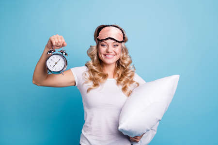 Portrait of her she nice-looking lovely attractive cheerful cheery wavy-haired lady showing retro vintage clock holding pillow isolated over bright vivid shine blue background