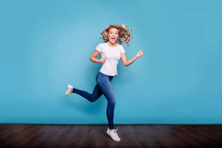 Full length body size view portrait of nice lovely attractive feminine cheerful cheery optimistic crazy wavy-haired lady in casual white t-shirt running fast isolated over blue background