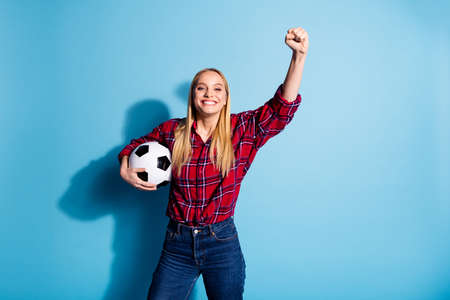 Portrait of her she nice charming attractive cheerful girl wearing checked shirt holding in hand black and white ball celebrating win isolated over teal turquoise bright vivid shine background