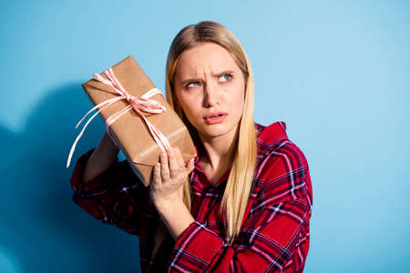 Close-up portrait of her she nice charming attractive sad puzzled lady in checked shirt guessing whats inside parcel shipment shadow isolated over teal turquoise bright vivid shine background