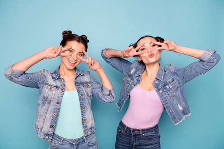 Portrait of attractive charming satisfied hipsters childish carefree isolated making v-signs coquettish flirting having casual vacation outside street wearing denim clothes on blue background