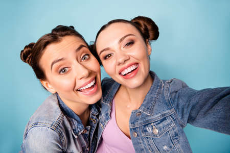 More photos. Close up photo of carefree childish charming satisfied buddies isolated spending free time together blogging dressed in denim outfit on azure background Foto de archivo - 120892999