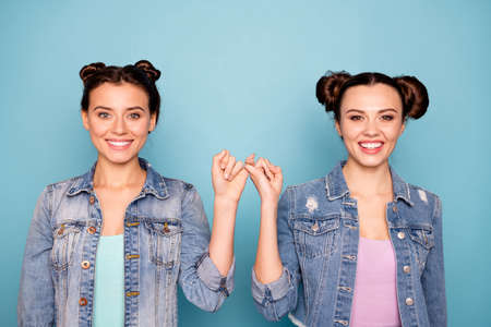 Portrait of cute charming satisfied hipsters person isolated holding hands together placing pinkies showing peace conciliation wearing modern denim clothing on pastel background Stockfoto