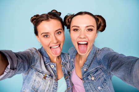 Close up photo of carefree childish cheerful teenage ladies making photos faces blogging isolated on free time enjoying dressed in denim jackets on pastel background Фото со стока