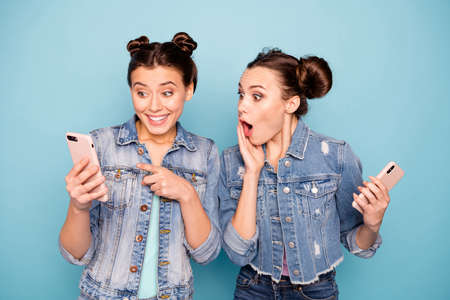 Portrait of excited impressed students people fellows use devices recommend select choose decide discount options screaming wow omg look wearing blue denim jackets pastel background isolated