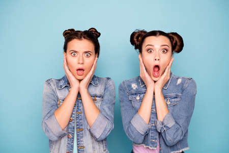 Close up photo of astonished upset confused ladies struck by horrible news information touching chin with hand opening mouth yelling saying wow dressed in denim outfit isolated on blue background