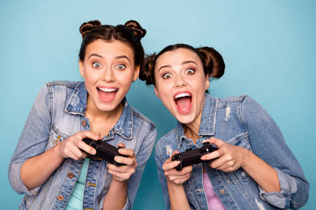 Close up photo of cute funky hipsters having free time game contest battle speed race using apps gamepad sitting indoors dressed in denim outfit on blue background