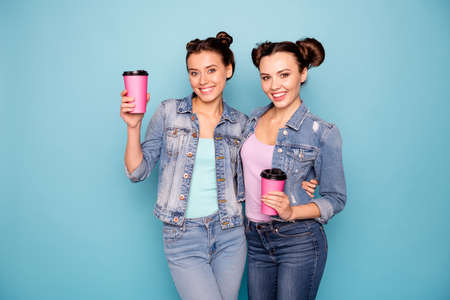 Portrait of cute charming millennial ladies isolated having refreshments take away go vacation in cafe dressed in denim clothing on azure background