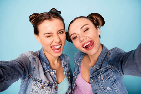 Unforgettable moments. Close up photo of crazy cheerful attractive teenagers taking photos blogging showing tongue out licking lips dressed in blue denim clothes on pastel background Stock fotó